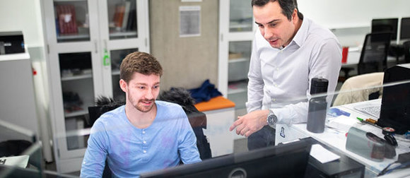 Jakub Kostal and student looking at computer