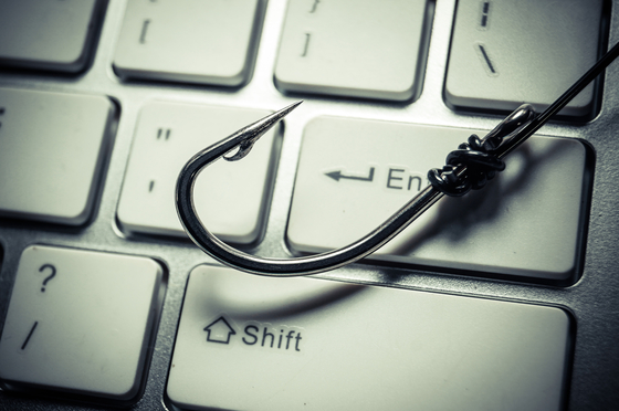 Photo of a computer keyboard with a fishing hook on it.