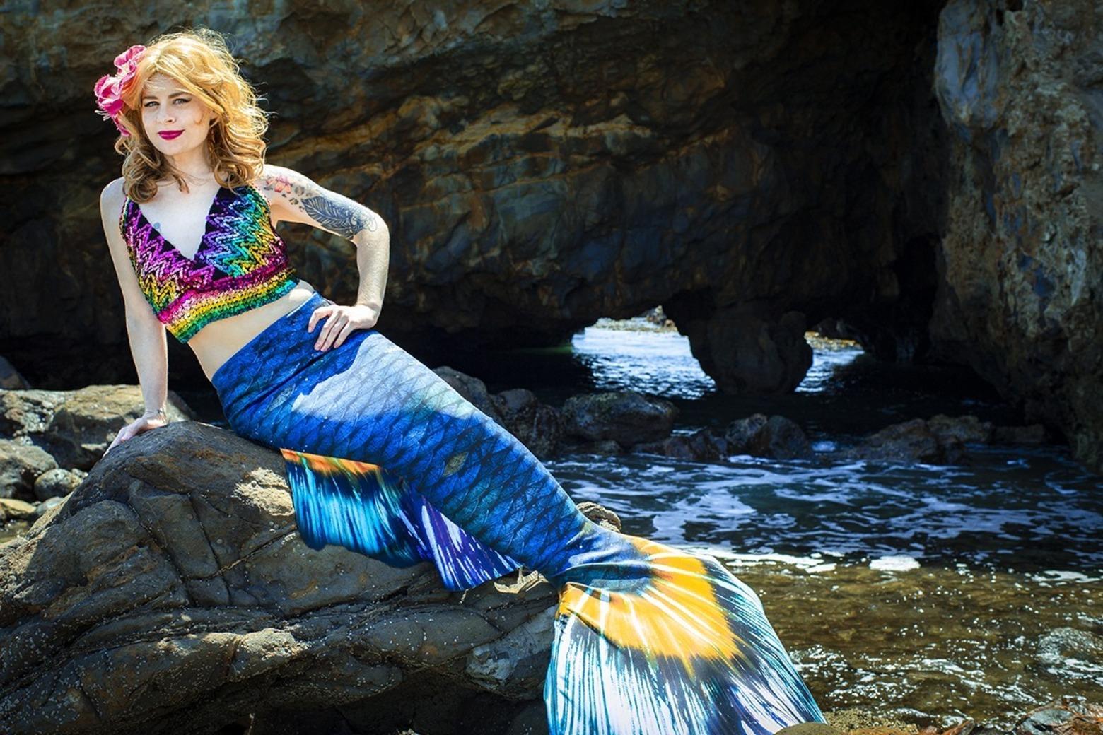 Mermaid Jinx sitting sideays on a rock in the Pacific Ocean