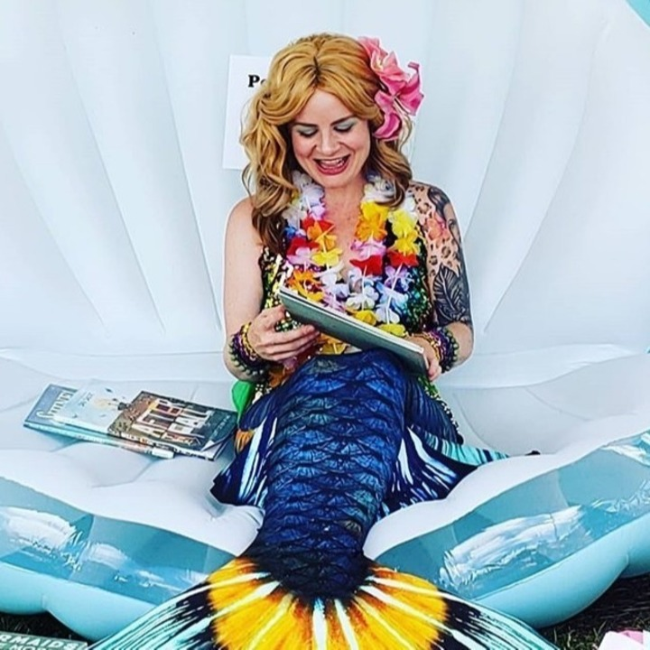 Mermaid Jinx Sitting on her Giant Clam Shell reading a book with other books lying next to her