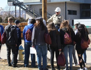 A lineman shows students how his job works on a pole