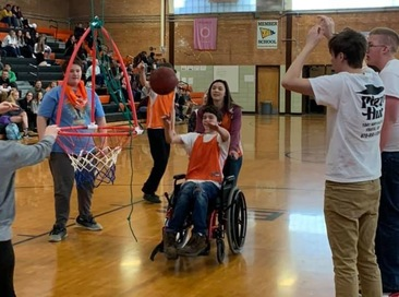 A student in a wheelchair shoots a free throw into a basket during a unified basketball game.