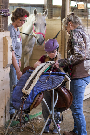 Image of TEC volunteers helping rider saddle up their horse.