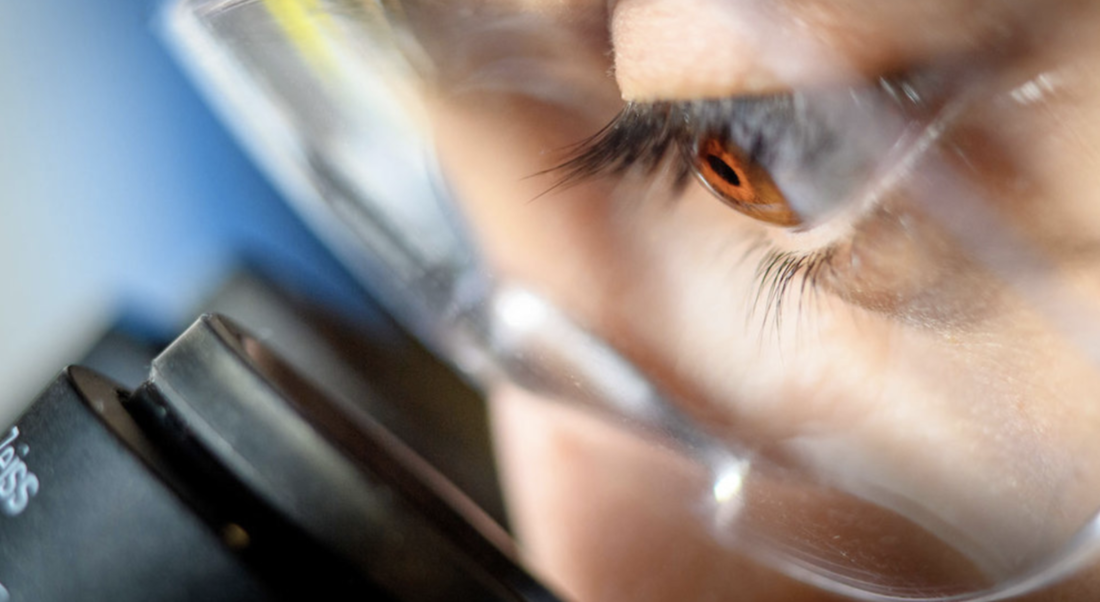 Photo of person looking into a microscope lens.