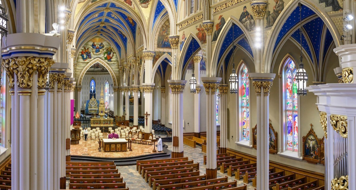 Photo of the inside of the Basilica, where a priest says Mass to no one in the pews.
