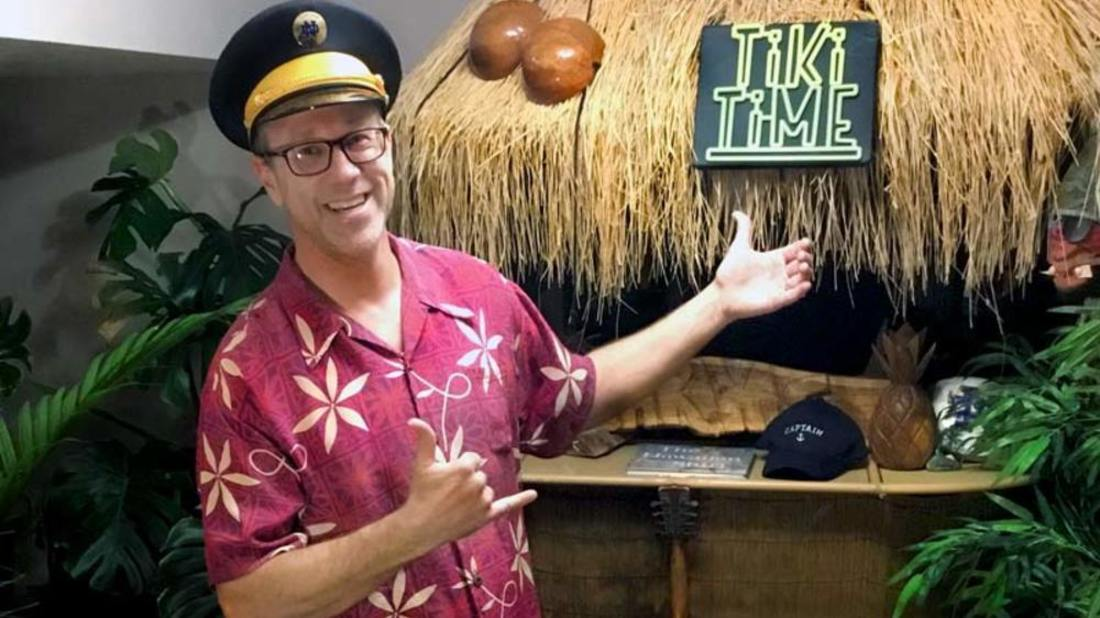 Professor Chad Harms wearing a Hawaiin shirt standing in front of a grass hut with a Tiki Time sign.
