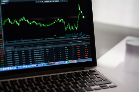 Photo of a laptop with stock market graph.