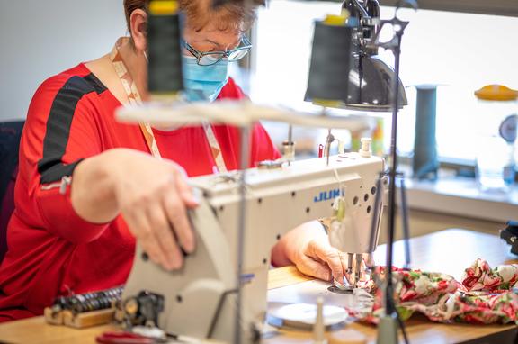 Photos of seamstress sewing masks.