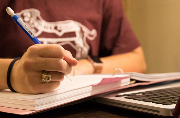 A student wearing a maroon shirt holding a pencil over a notebook with a laptop nearby