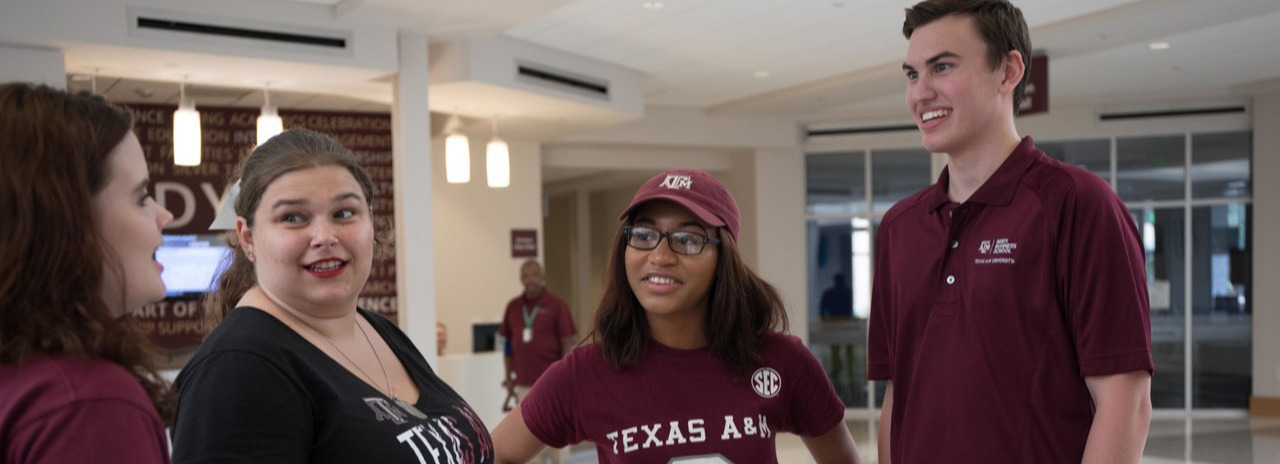Four students wearing Aggie gear stand in a building talkiing