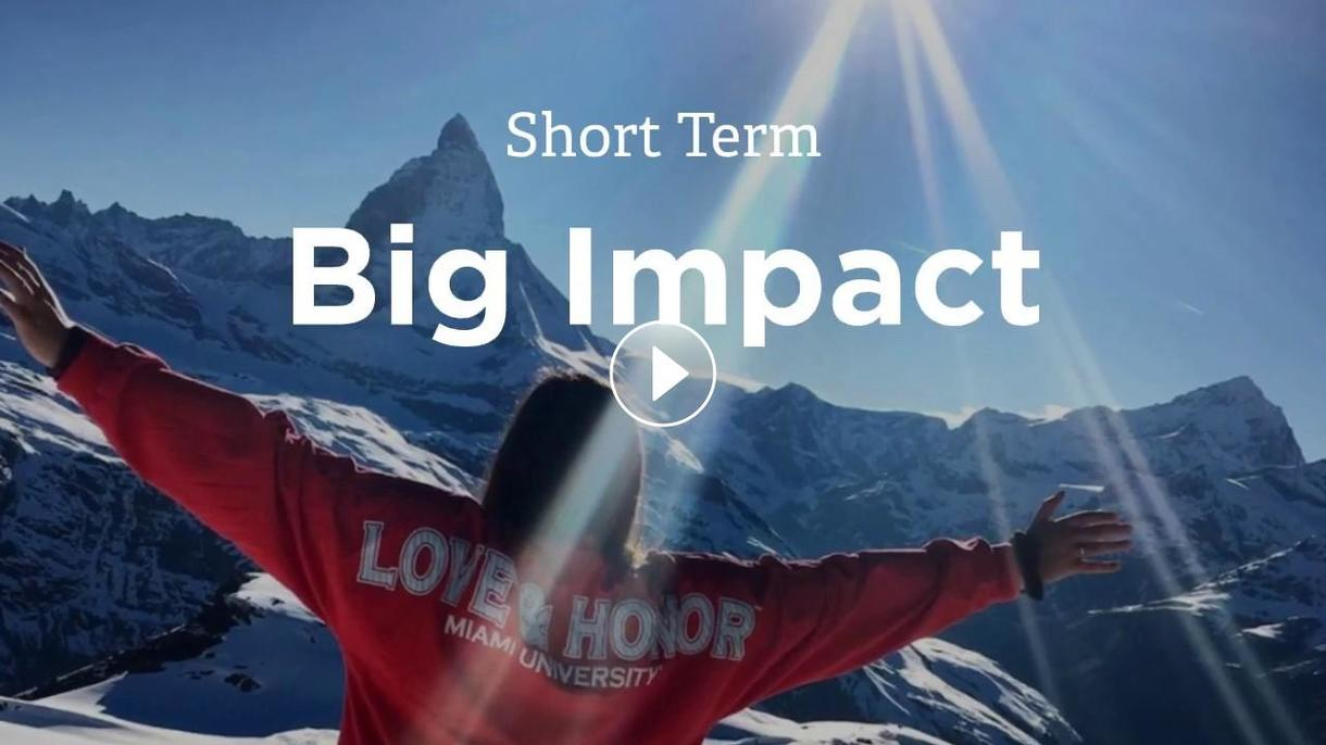 Short Term Big Impact. A student wearing a Miami love and honor shirt is seen with arms outstretched in front of a mountain