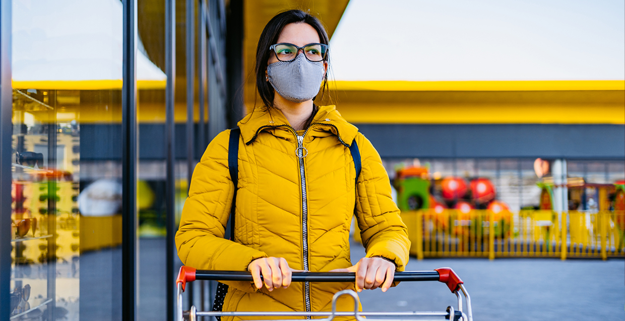 A woman in a yellow jacket wearing a cloth face mask while grocery shopping