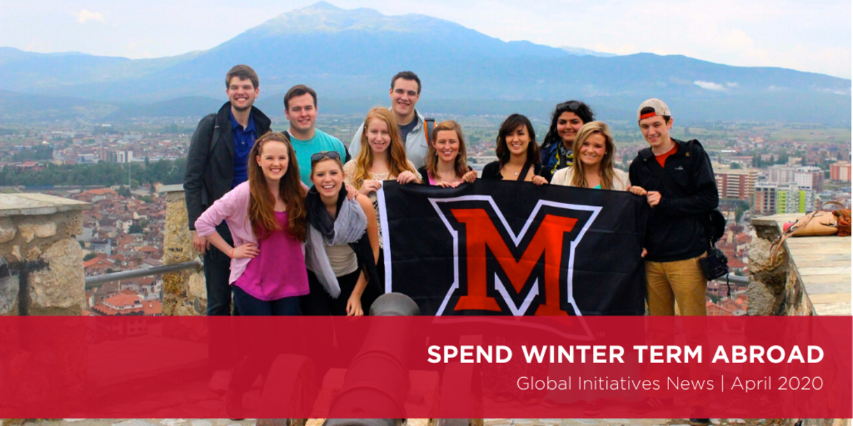 Students hold a Miami flag with mountain in background