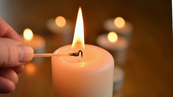 a person lighting a candle