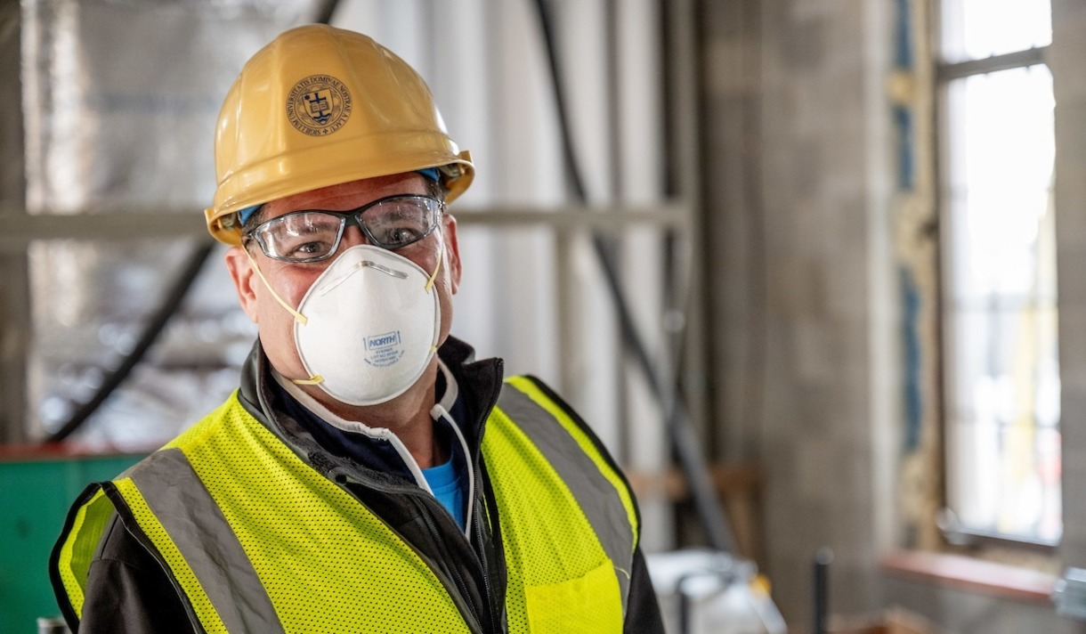 Tony Polotto, director of quality assurance, poses at a construction site with a mask on his face.