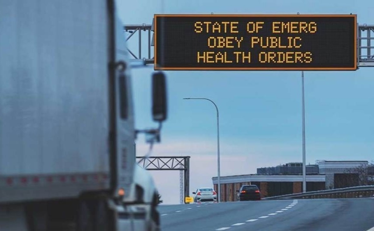 Photo of sign on highway that warns of health state of emergency.