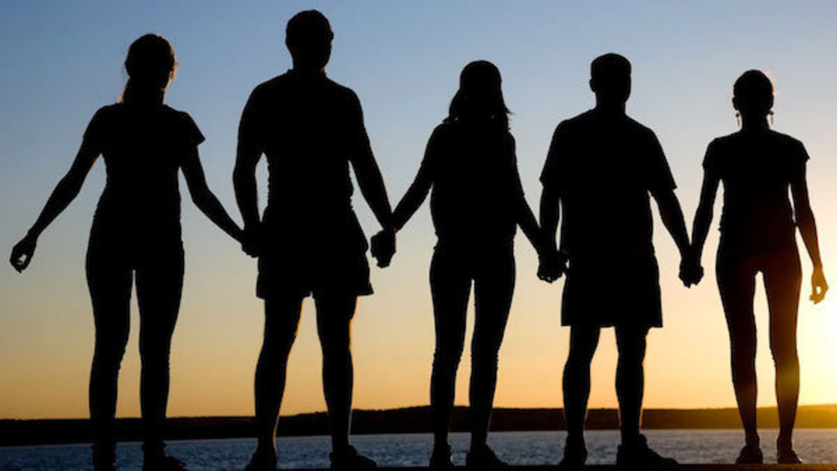 Silhouette of students holding hands at sunset