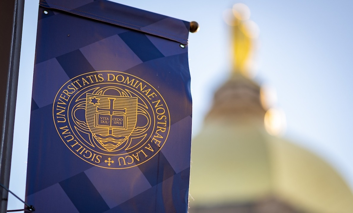 Photo of banner with University seal and Main Building in background.