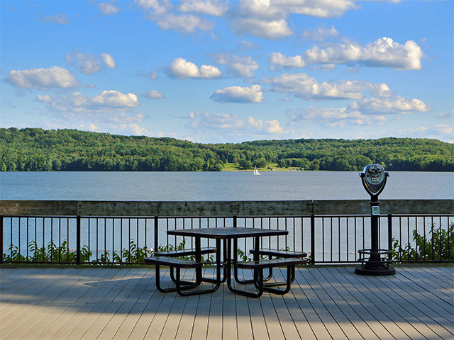 Picnic table on a wodden deck overlooks a lake
