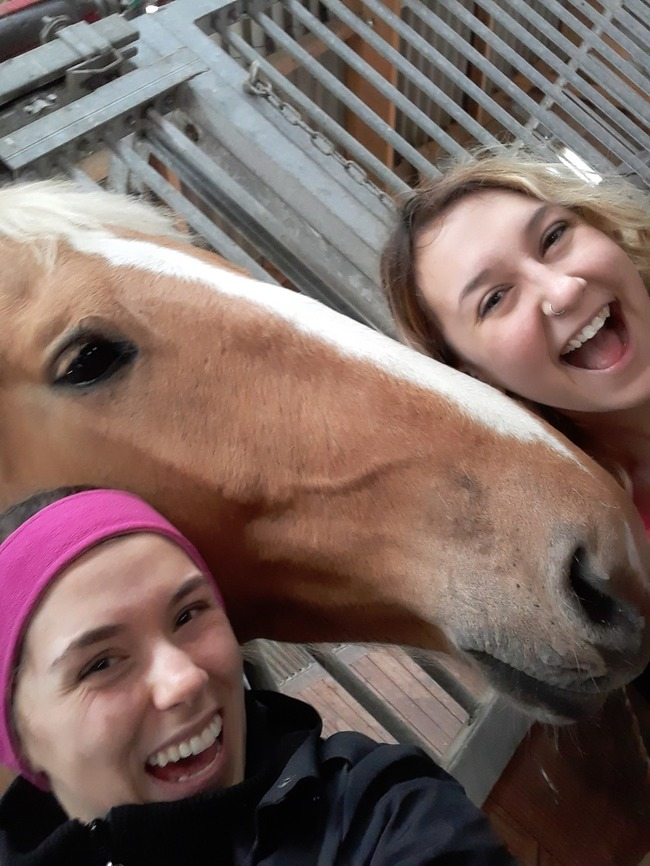 Hailey Kingsbury and Lauren Kramer take a picture with a horse