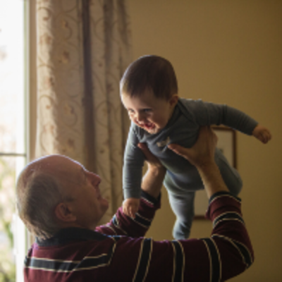 Old man holding up baby