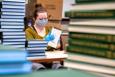Notre Dame employee assembles memory box for graduates.