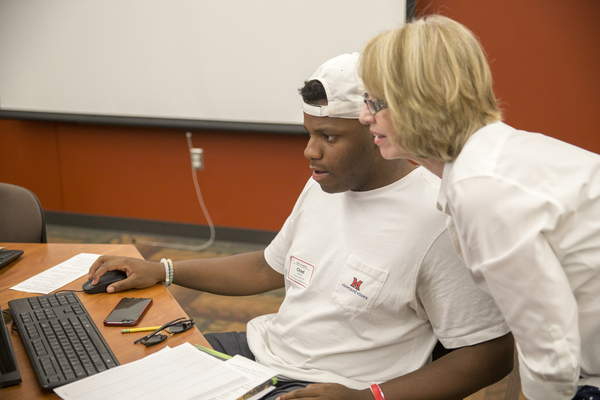 Assistant Dean, Roxann Sommers working with a student who she is advising. They are both looking at a computer screen.