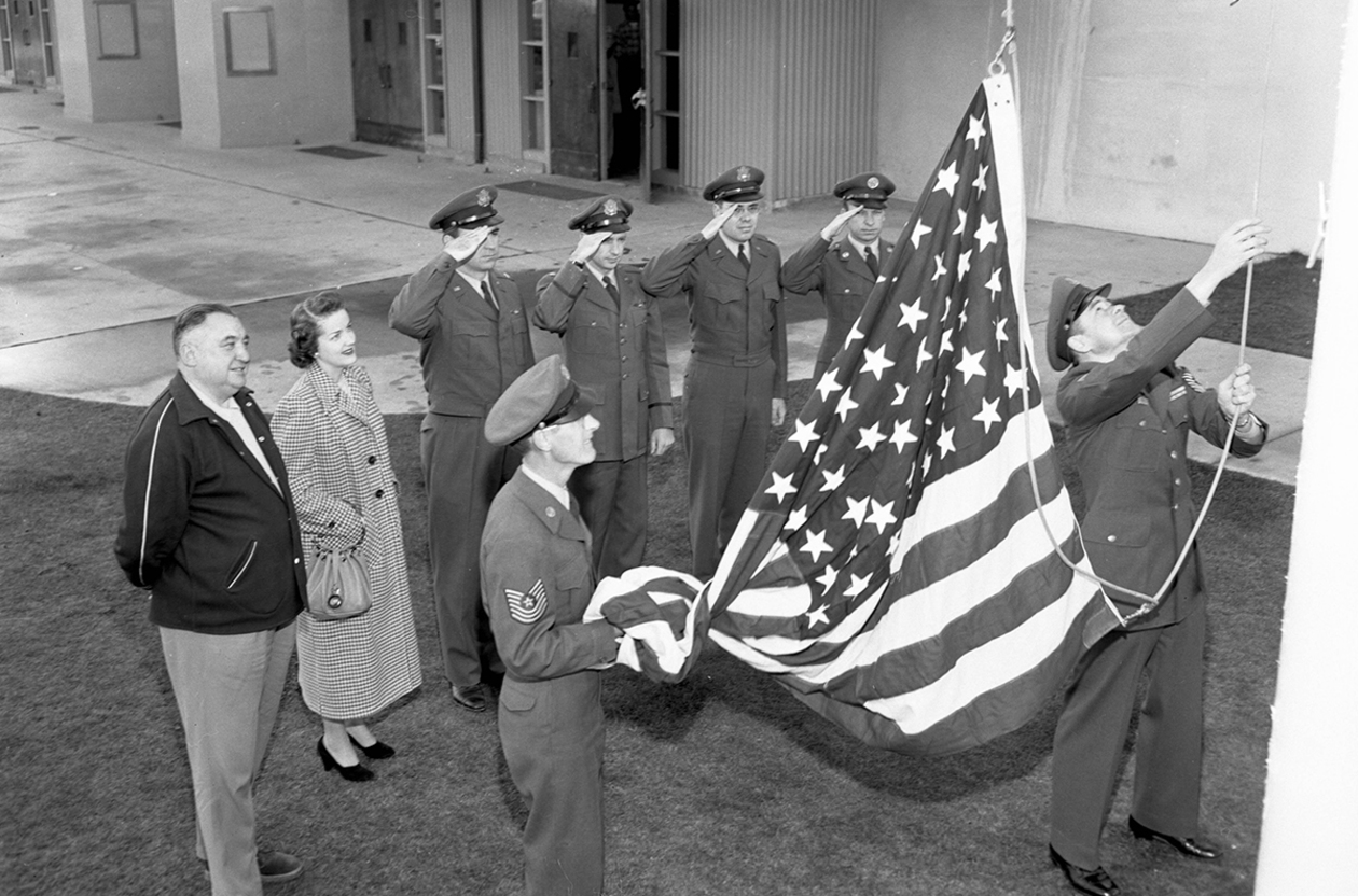 Archive photo of AFROTC officers raising the American flag outside of Memorial Fieldhouse in 1951.