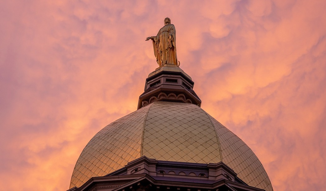 Photo of the golden dome of Main Building at the University of Notre Dame taken at dawn.