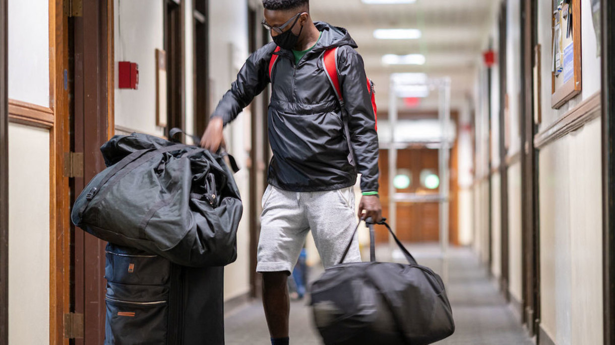 A student, wearing a face mask, is carrying luggage down a residential hall.
