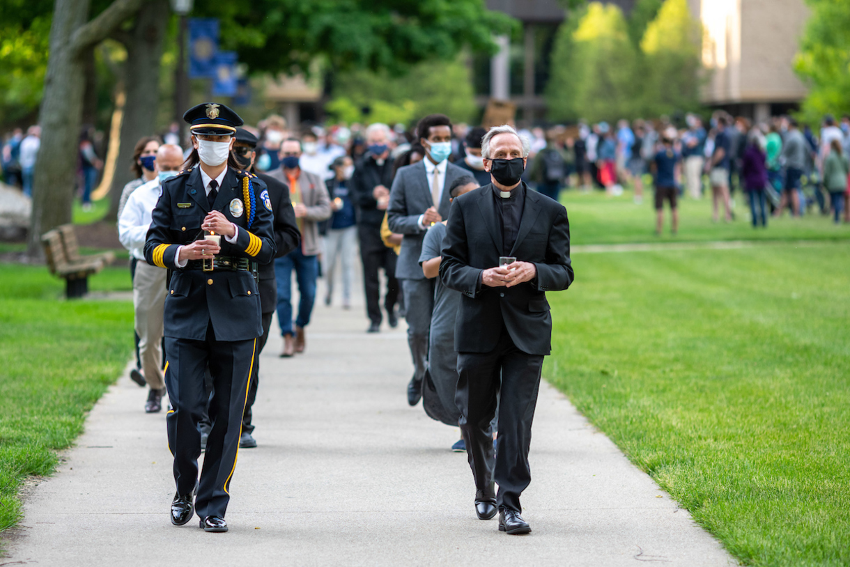 A photograph of ND Chief of Police and Father Jenkins leading others in walk to the Grotto.