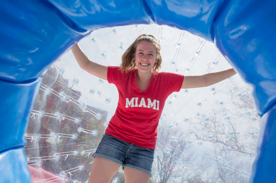 student in an inflatable ball -- wearing a Miami t-shirt