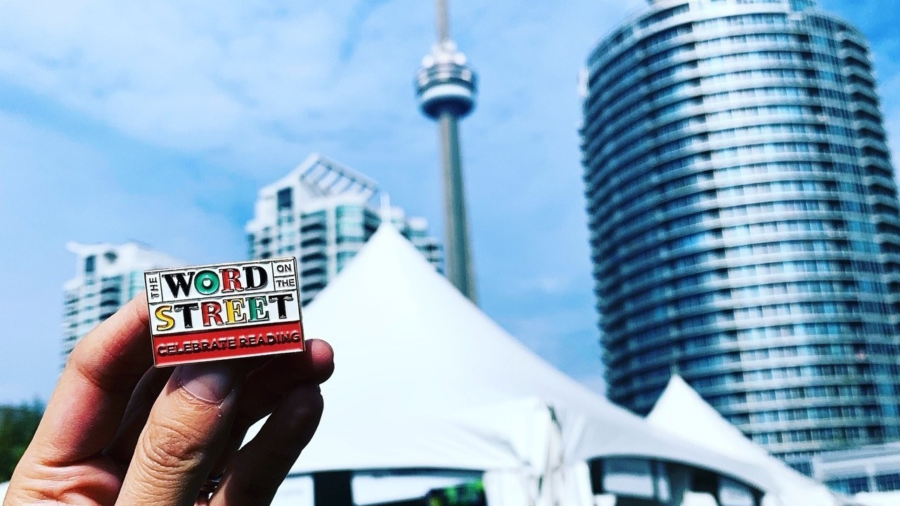 The Word On The Street's 'Celebrate Reading' enamel pin against the Toronto skyline. Photo by @justalillost