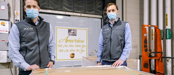 Alumni Chris Kiple (l) and Chris Brooks signed the box for the first shipment of VOCSN ventilators from the Ventec Life Systems/GM facility in Kokomo, Ind.