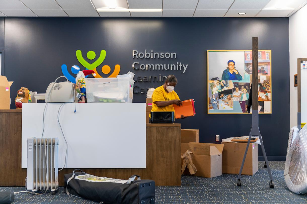 Photo of RCLC employee unpacking folders.