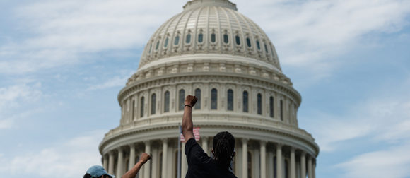 Protestors raising fists in front of the Capitol building