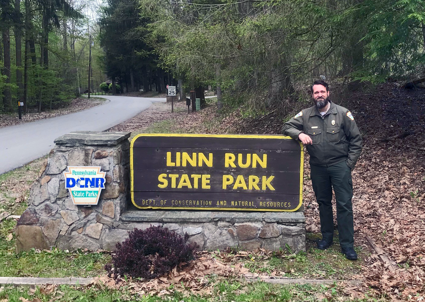 Corey Snyder stands next to the Linn Run State Park sign