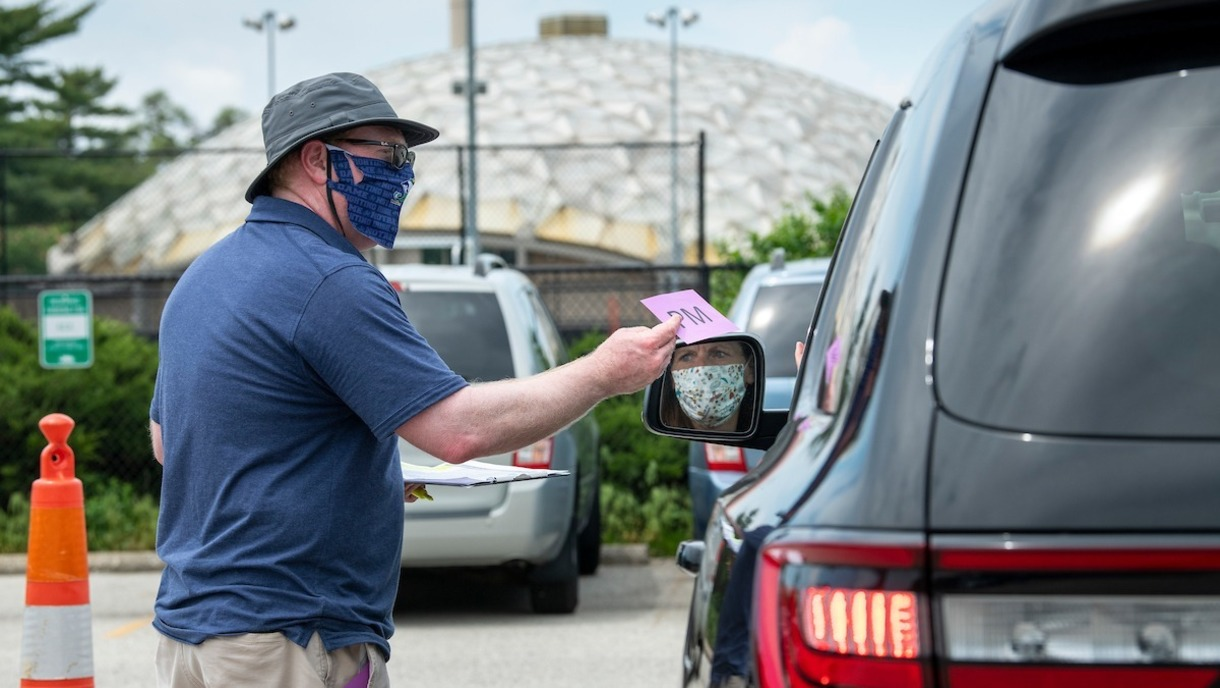 Photo of man in a face mask standing next to a van.