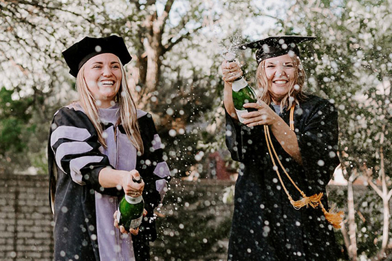Two students pop Champaign bottles to celebrate commencement.