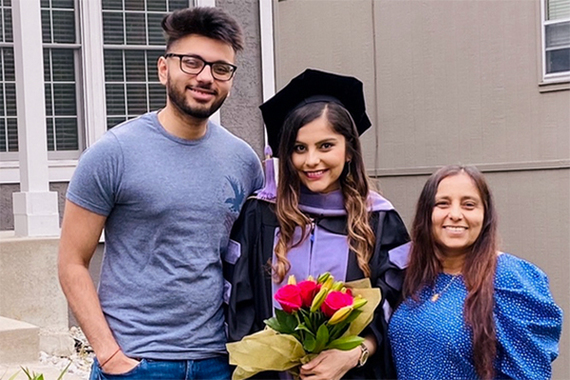 Student shown with family members celebrating pre-commencement.