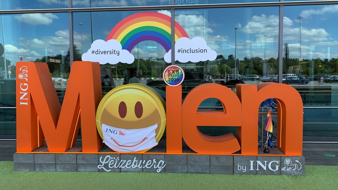 Moien sign in front of Luxembourg airport with smiley emoji wearing a mask