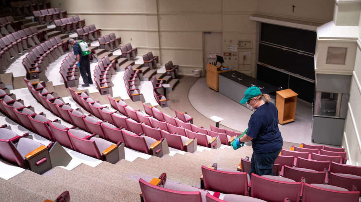 Building Services worker disinfects classroom auditorium.