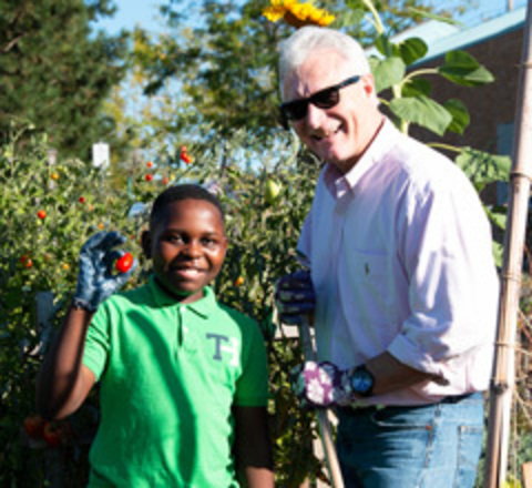 A man and his young mentee garden together.