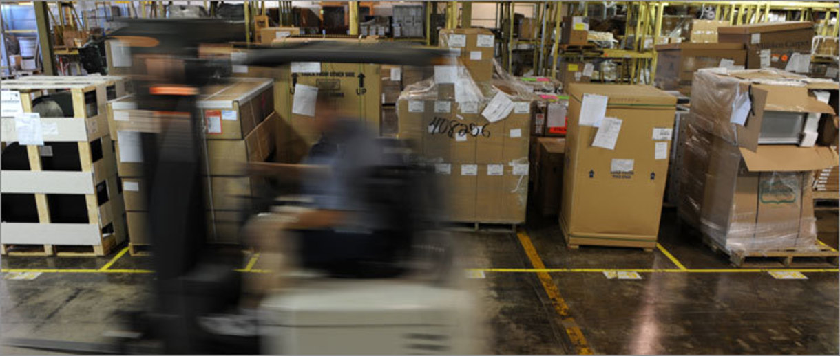 A photo of a warehouse and a person driving a forklift