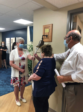 Golisano Medical Oncology Center patients Carol Faccini, Margaret Tretter and John Gabriele join to ring the Victory Bell at the dedication ceremony, in a symbolic act that that officially opened the new Center.