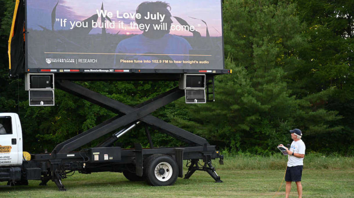 Vice President of Research Bob Bernhard stands in front of a huge prortable movie screen on the back of a semi-truck at St. Pat's Park on July 7, 2020.