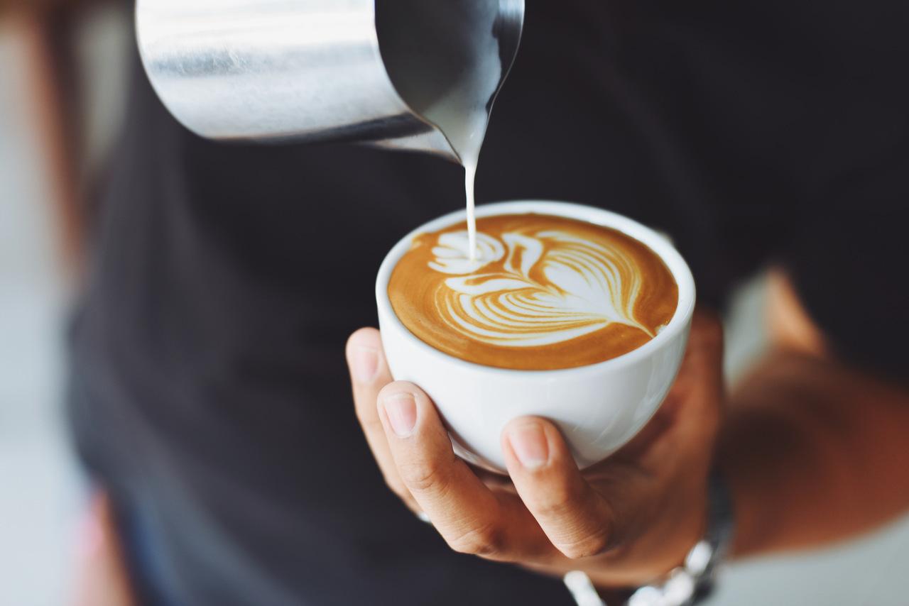 Person pouring a latte