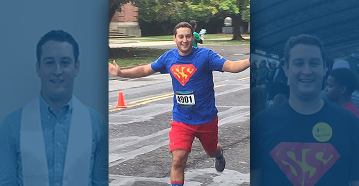 Sean crosses a finish line with his hands out wide in accomplishment.
