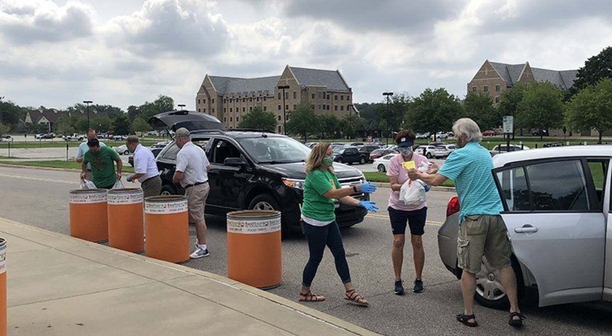 Photo of people and cars and food being donated.