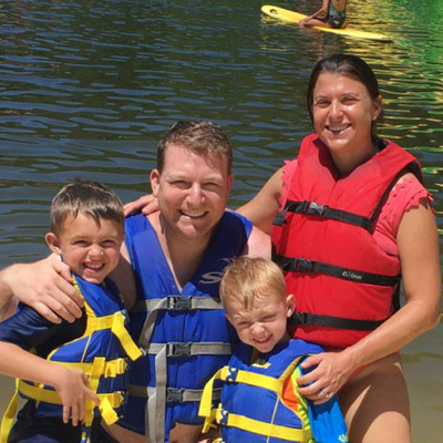 Photo of family in lake at Capital Camps Retreat Center wearing life vests for water sports.